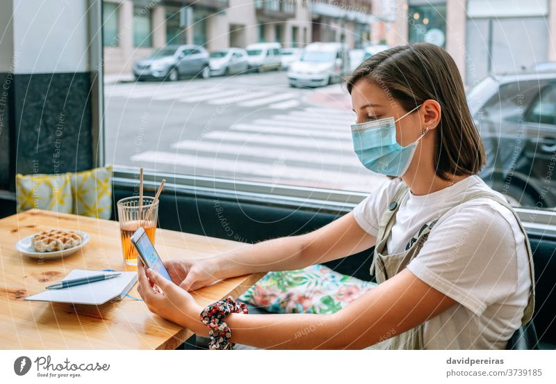 Woman with mask having a snack in a coffee shop cafe woman covid-19 coronavirus protective mask new normal breakfast mobile cafeteria surgical mask girl people