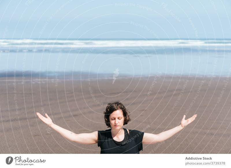 Slim woman doing meditation on beach yoga sea practice asana pose eyes closed sit balance calm seashore harmony arms raised wellness lifestyle flexible female