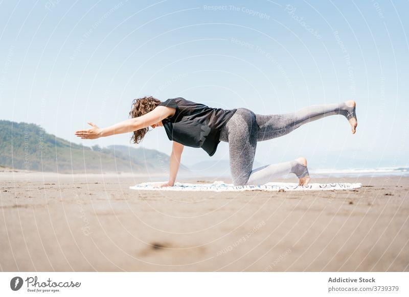 Slim woman doing yoga pose on the beach sea practice asana balance calm seashore harmony wellness lifestyle flexible eyes closed female nature vitality activity