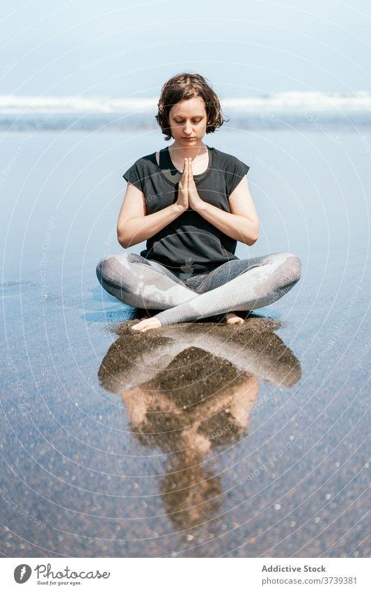 Slim woman doing meditation on beach yoga sea practice asana pose twist eyes closed sit balance calm seashore harmony wellness lifestyle flexible female nature