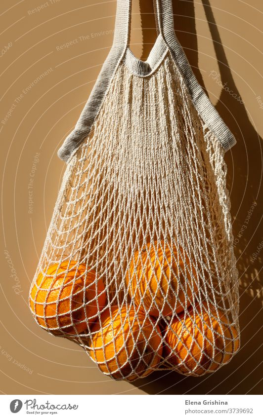 Ripe oranges in a white string bag. Beige background. zero waste eco shopping beige reusable concept ecology cotton market vegetarian no plastic economical