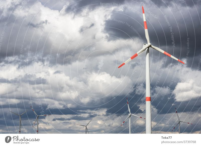 modern wind wheels in front of a cloudy storm sky wind turbine wind turbines cloudy sky stormy sky clouds storm clouds green energy wind energy electricity