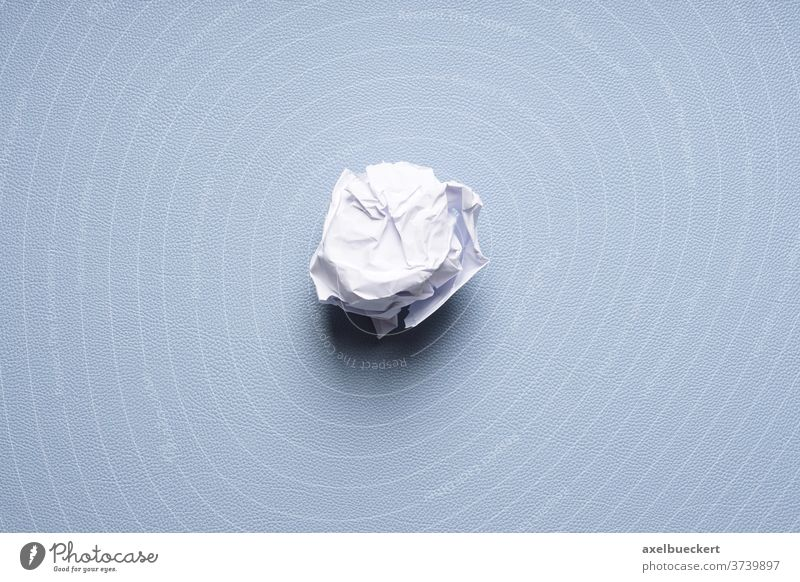 crumpled-up ball of paper on blue background balled discard dispose scrap throw away concept fail problem idea desk pad sheet trash rejection scrunch wastepaper