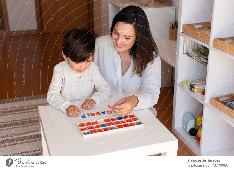 Kid learning to write and read with a alphabet and mother or teacher help. Homeshooling. Learning Community. Montessori School letters educator caucasian desk