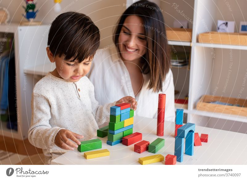 Preschooler Kid playing with wood blocks and teacher educador help. Homeshooling. Learning Community. Montessori School wood toys game educator mother caucasian