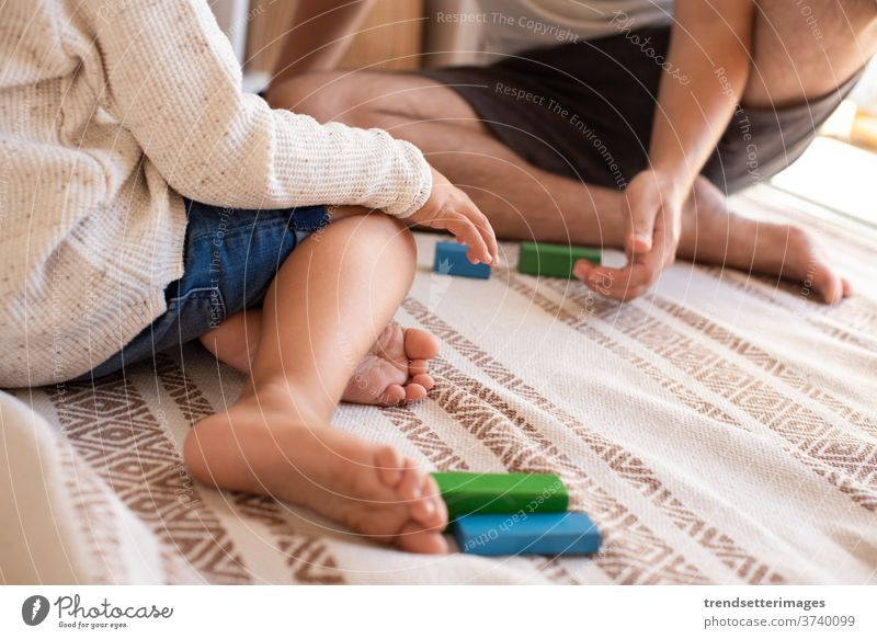 kid and his father playing at home with wood building blocks. Homeschooling. Stay at home. Family time covid-19 safe coronavirus stay at home quarantine family
