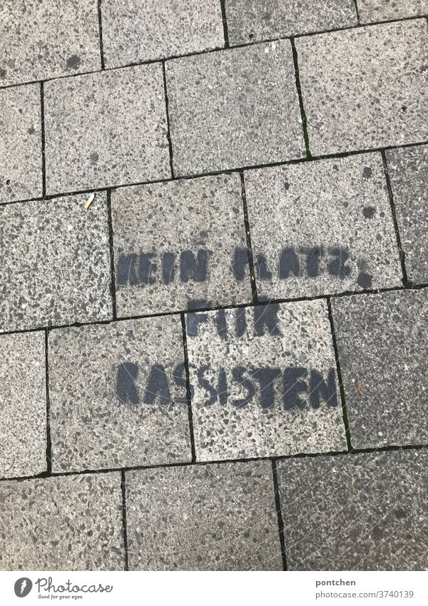 No room for racists on cobblestones on the floor. Embassy, streetart. anti-racism. Racism embassy resistance politically Attachment street art Characters