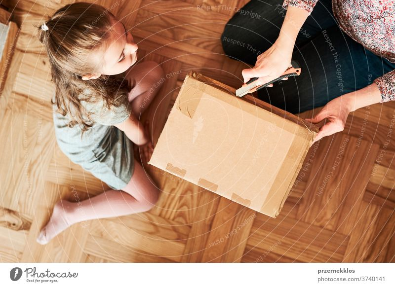 Woman unpacking a cardboard box parcel in room at home. Little girl waiting for opening a gift in package view floor unboxing tape daughter woman filler foam