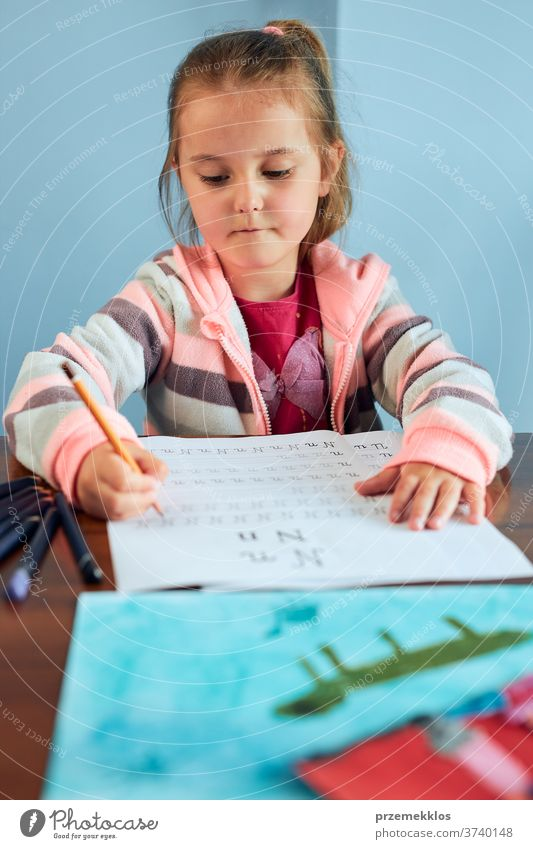 Little girl preschooler learning to write letters at school. Kid writing letters doing a school work. Concept of early education attention caucasian child