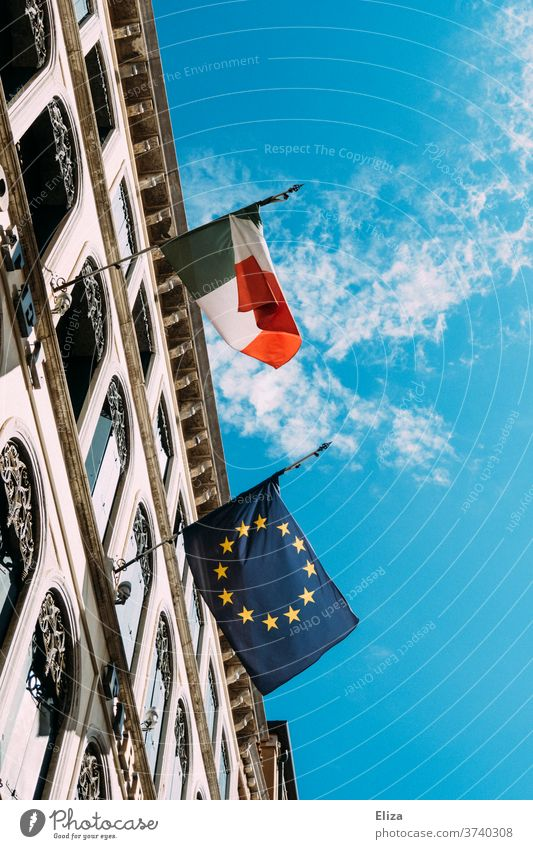An Italian and a European flag hang next to each other on a building and flutter in the wind Italy hoisted built Sky Flag Politics and state Ensign Blow