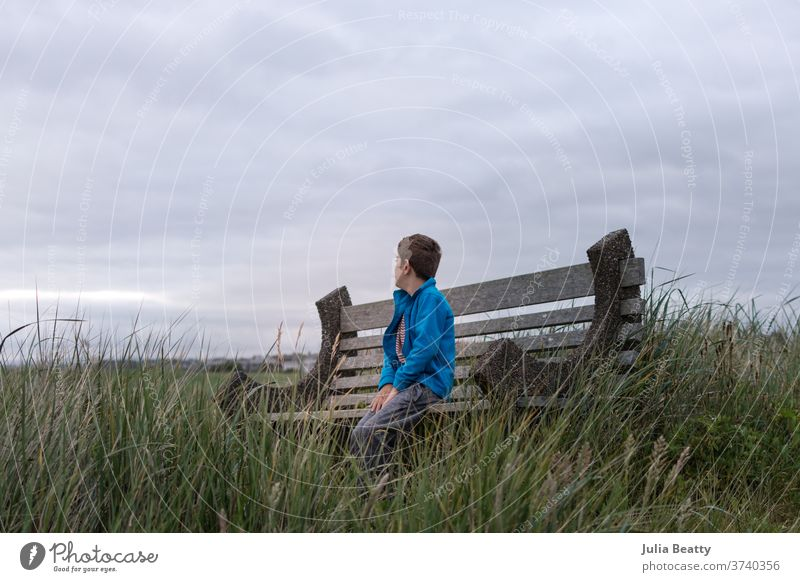 boy on a bench at the seaside ocean ocean view cloudy clouds solitude alone grass beach grass vacation pacific ocean Oregon United States summer cool reeds