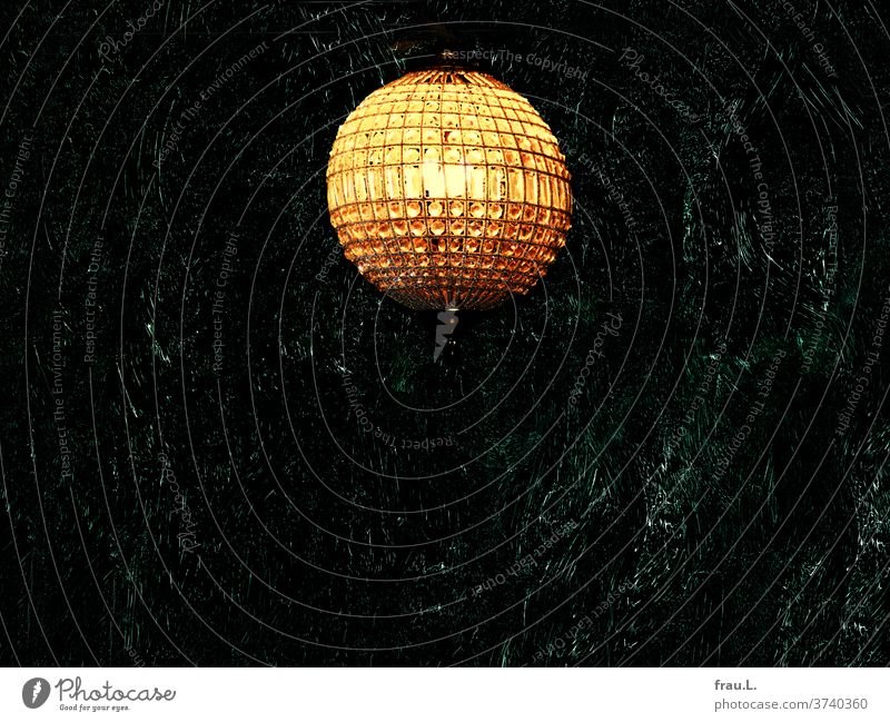 """I am a moon"", the golden yellow crystal lamp clinked and basked in its own light in front of the dark wall. Lamp chandeliers Glass Living or residing"
