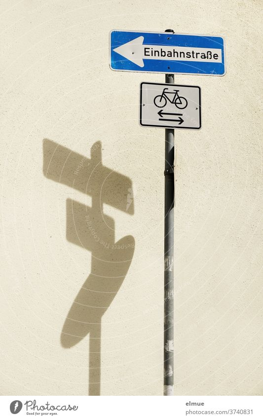 "Shadow play of a three-part traffic sign ""one-way street"" / ""cyclist"" / ? Road sign One-way street cycle path Traffic infrastructure Signs and labeling"