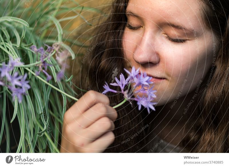 Young girl sniffs the garlic flower with relish Young woman Nose Fragrance flavor Odor Garlic Intensive Garden flowers natural Nature sharp spicy To enjoy