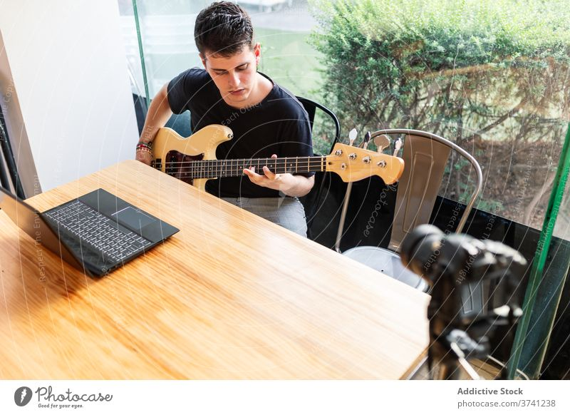 Young man playing bass guitar music accord skill perform musician instrument sound melody song hobby young male learn lifestyle guitarist practice talent string