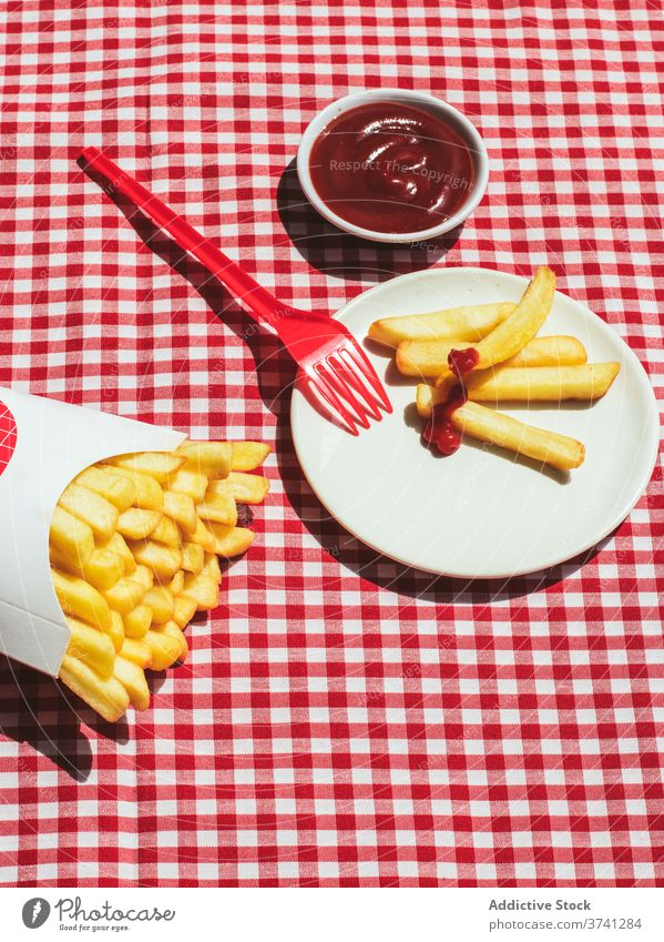 French fries packet near plate with potatoes soaked in ketchup american culture condiment potato chips unhealthy eating red background white frites take out