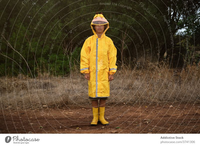 Portrait of a boy in a yellow hooded raincoat and rain boots standing outdoors schoolboy hide wear protective way comfortable trendy security stylish wet