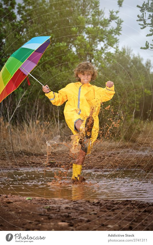 Boy with boots and raincoat holding an umbrella and playing in a puddle joke schoolboy shower attitude rainbow curly gesture splash enjoyment pouring wet