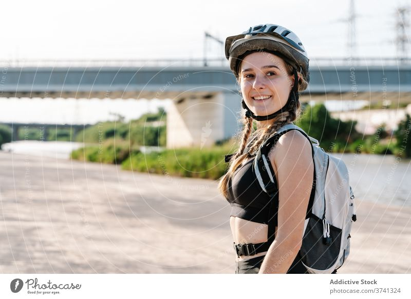 Portrait of slim young female in sportswear looking at camera woman cyclist sporty activity rest helmet exercise bottle biker break thirst healthy lifestyle