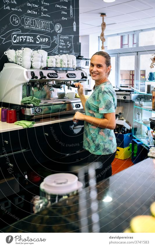 Female barista preparing coffee machine woman coffee shop coffee maker happy looking camera waitress cup cafeteria drink dishcloth business job professional