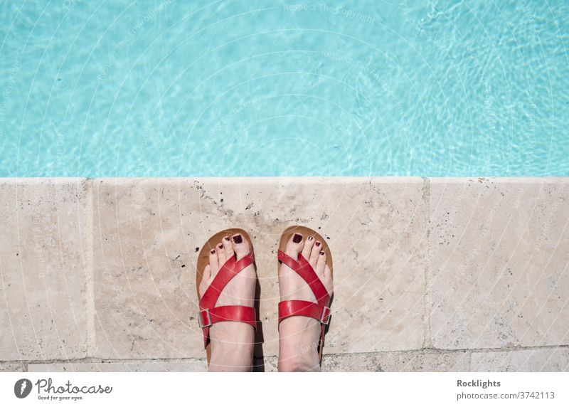 Feet in red sandals by the edge of a swimming pool color colorful pair space sun leisure shoe footwear fashion feet background bare blue bright concept feel