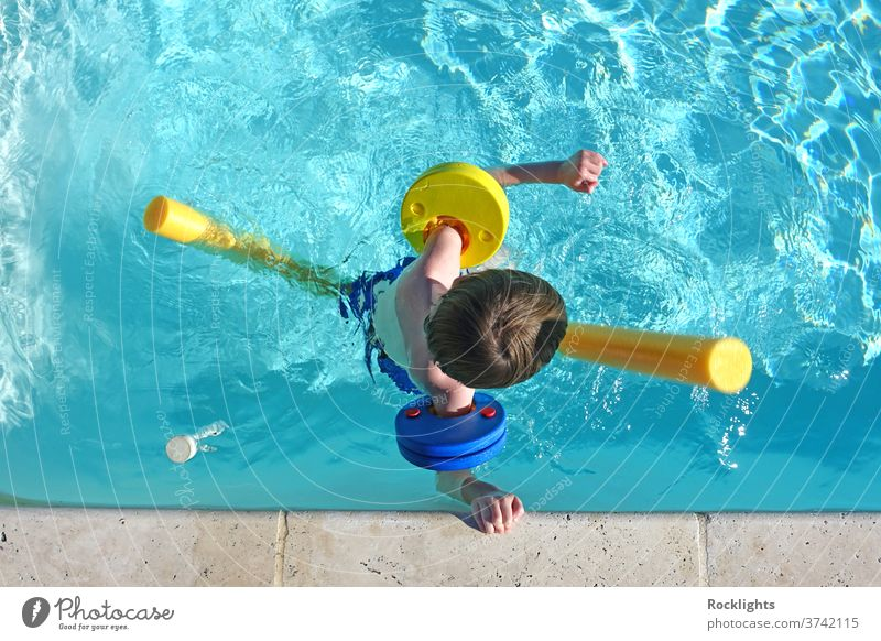 Top view of little boy floating in swimming pool with floats and arm bands vacation holiday kid happy lifestyle young healthy recreation active play above aids