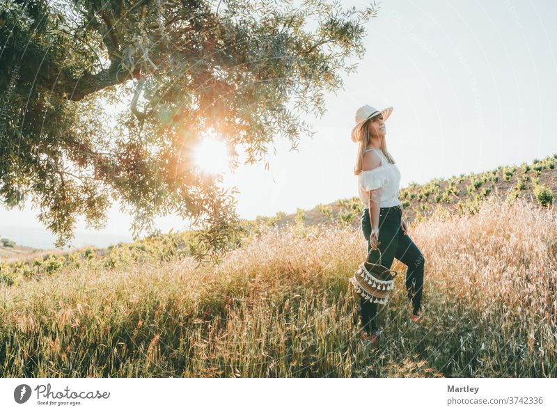 Young woman with a straw hat and a basket walking through the field at sunset in summer. Concept of freedom, tranquility, nature, ecology, green world and happiness.