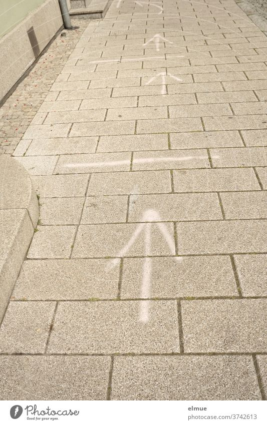 white arrows and lines on the sidewalk illustrate the distance control during corona gap Arrow Distance control off coronavirus Footpath risk of contagion