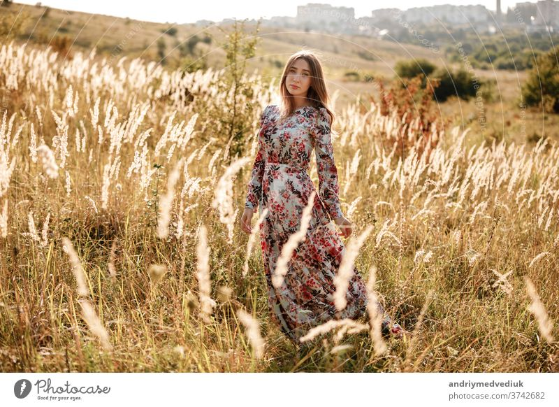 beautiful young woman in dress in field at sunset. stylish romantic girl with long hair having fun outdoors. summer beauty nature free meadow model fashion
