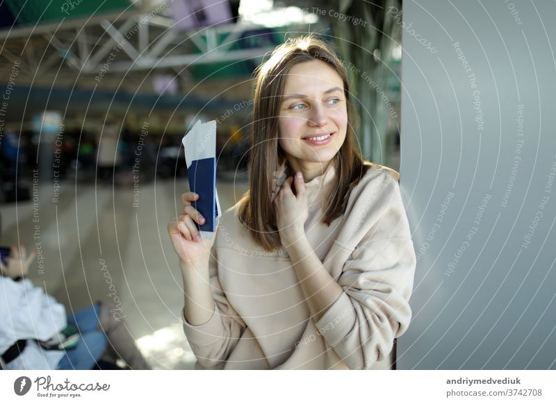 portrait of happy young woman holding passport and boarding pass at airport flight girl travel traveller passenger female journey trip beautiful pretty