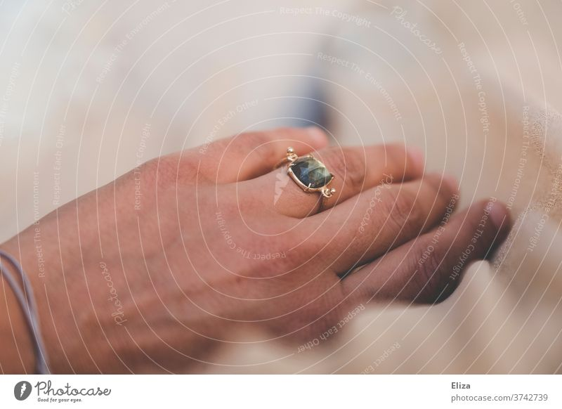 A hand with a golden ring with a green shimmering stone on the ring finger Ring finger Gold Stone by hand Jewellery Woman Detail Accessory White Bride