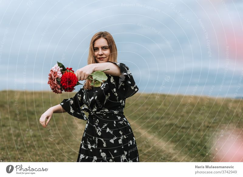 Woman holding flowers in hand outdoors in nature adult attractive beautiful beauty cute dress face fashion female field flower wreath freedom girl grass green