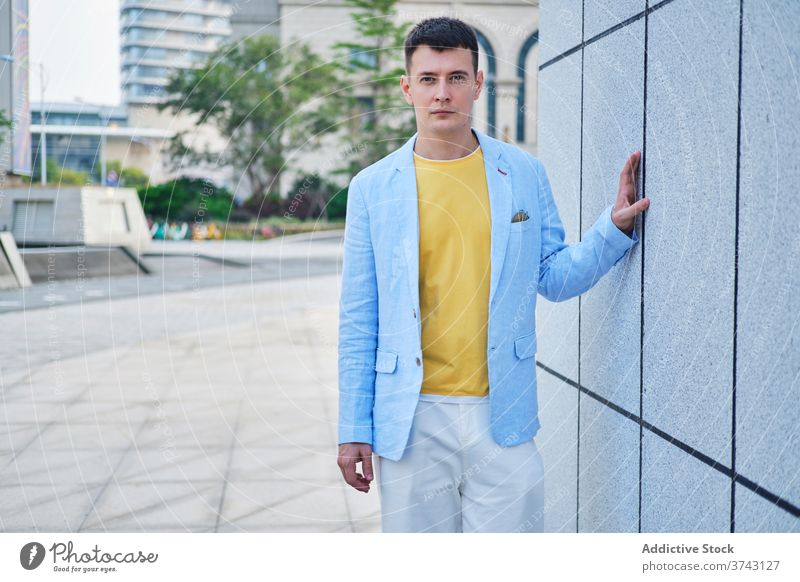 Young man on the street leaning on wall and looking at camera adult portrait background blue yellow male lonely minimal mood sense style think vintage depth