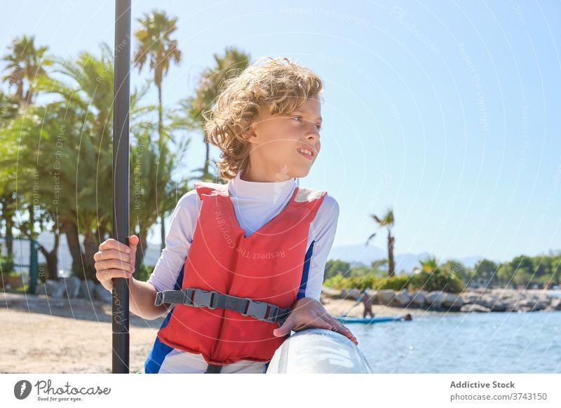 Distracted boy wearing a vest leaning against a paddle surfboard and holding the paddle stick rescue exercise kid outfit surfing tranquility exercising protect