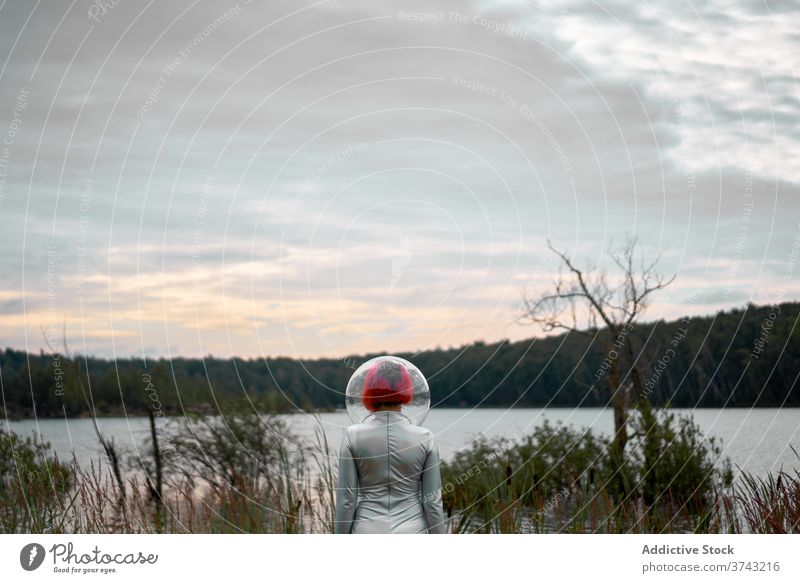 Woman in astronautic suit walking to water woman futuristic space helmet river nature cosmonaut concept female silver future fantasy science explore planet