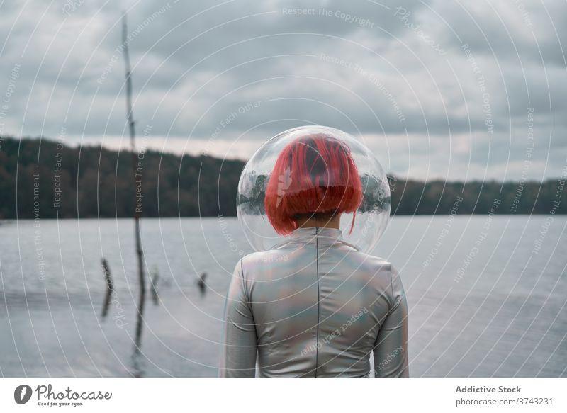 Woman in astronautic suit walking on water woman futuristic space helmet river nature cosmonaut concept female silver future fantasy science explore planet