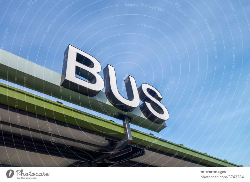big white physical bus sign type all capital letters bus station transportation station bus stop company business logo exterior corporation office building