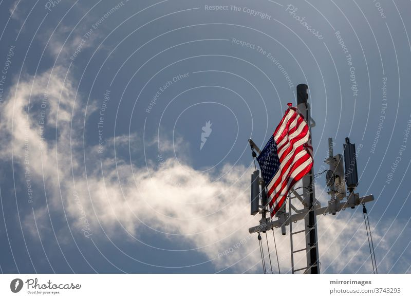 United States of America Flag Blowing in the Wind on the deck of a large ship at sea with cell towers america american banner battleship blue boat breeze