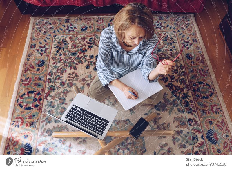 Middle age senior woman working at home using computer female laptop mature people one house person lifestyle eyeglasses attractive relax technology job