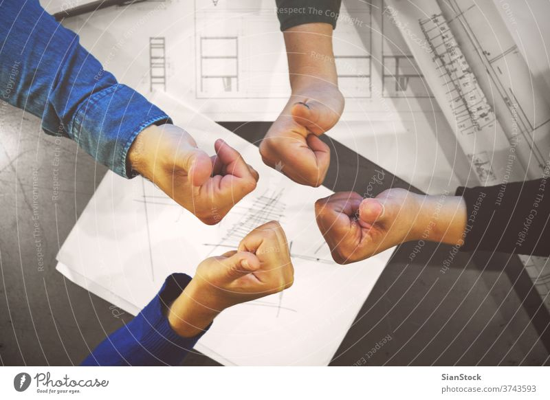Successful young business team giving thumbs up to show their success and motivation, close up view of their raised hands people joining like teamwork group