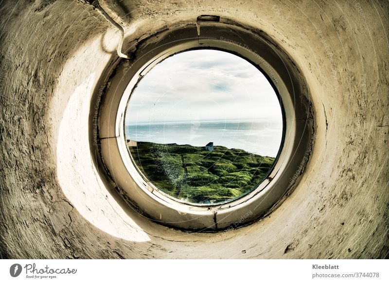 Through a round porthole of the lighthouse the view to the sea Lighthouse round window Porthole roughly plastered wall grey-white colour old parent