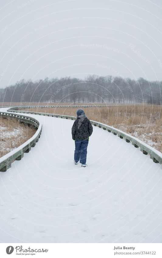 child walking on snow covered path in woods cloudy clouds solitude alone grass vacation Oregon United States reeds native plants Vacation & Travel Nature USA
