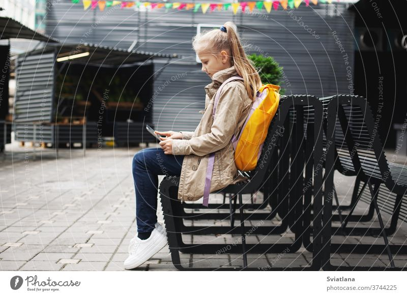 After school, a cute girl sits on a bench waiting for the bus, studies on a tablet online and communicates via video. backpack street schoolgirl learning