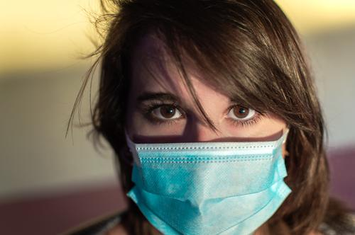 Close up of young woman using surgical mask and looking at camera. person corona stare coronavirus portrait eyes face wearing sunshine sunny use millennial