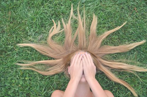 girl lying on a green lawn with hands in front of her face youthful Puberty hair Lawn reclining hands in front of your face Youth (Young adults)