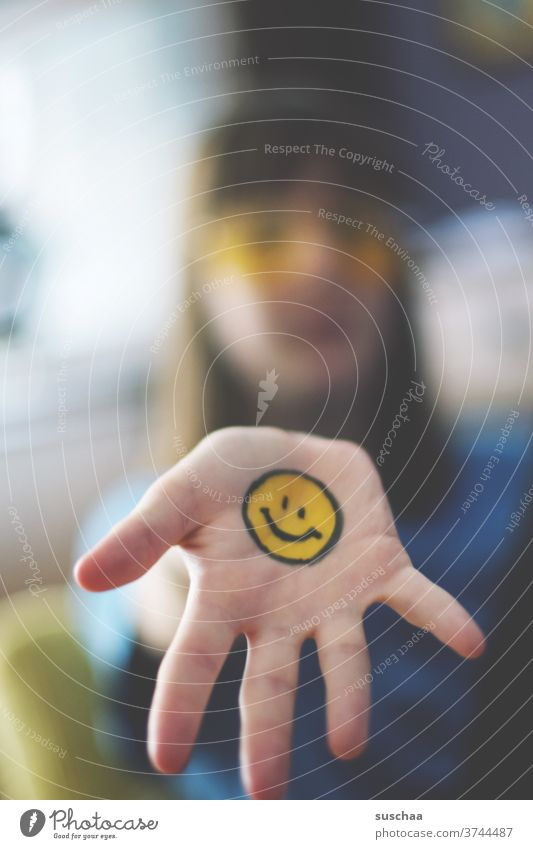 teenager with painted smiley face on hand Smiley Emotiocon emoji Sign Face Happiness Laughter Emotions Funny Joie de vivre (Vitality) Optimism Moody Contentment