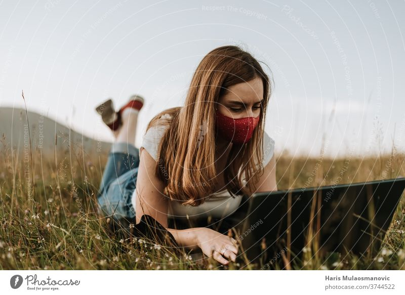 Woman with mask working remotely outdoors on laptop adult attractive beautiful corona cute daily routine face mask fashion female freelancer hair happy hat
