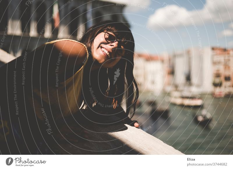 Woman leans over the railing of the Rialto Bridge to hold her face in the sun tourist Sun Venice Laughter Italy Channel Port City Joy Eyeglasses brown-haired