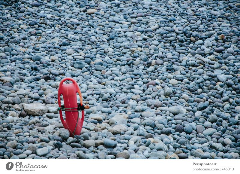 Red plastic buoyancy aid in the sand on lonely beach background torpedo water summer sun guard coast safety tube rescue lifeguard red equipment float protection