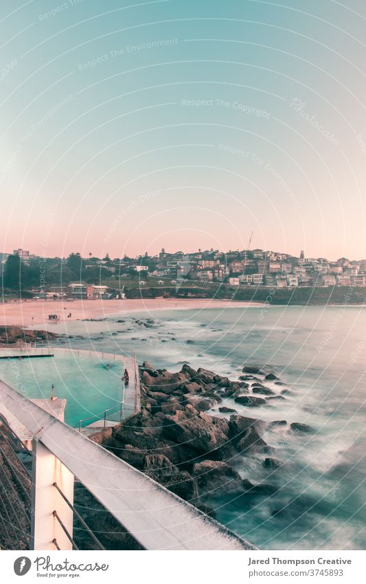 A pink spring sunrise overlooking Bronte Baths in Sydney, Australia. bronte baths ocean pool pools australia nsw newsouthwales eastcoast beach rocks summer